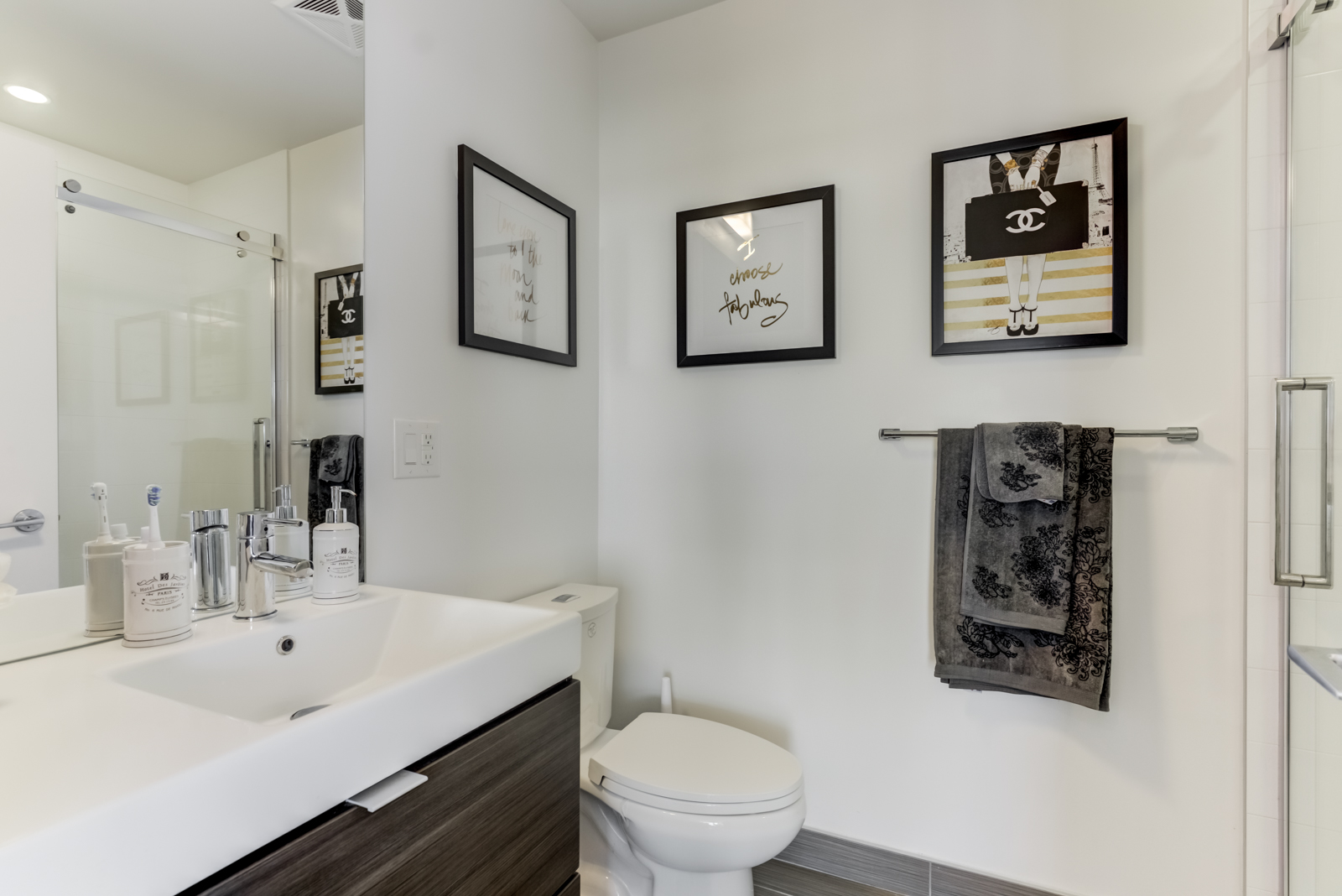 Second bathroom with dark picture frames, dark towel, white sink, and tall mirror.