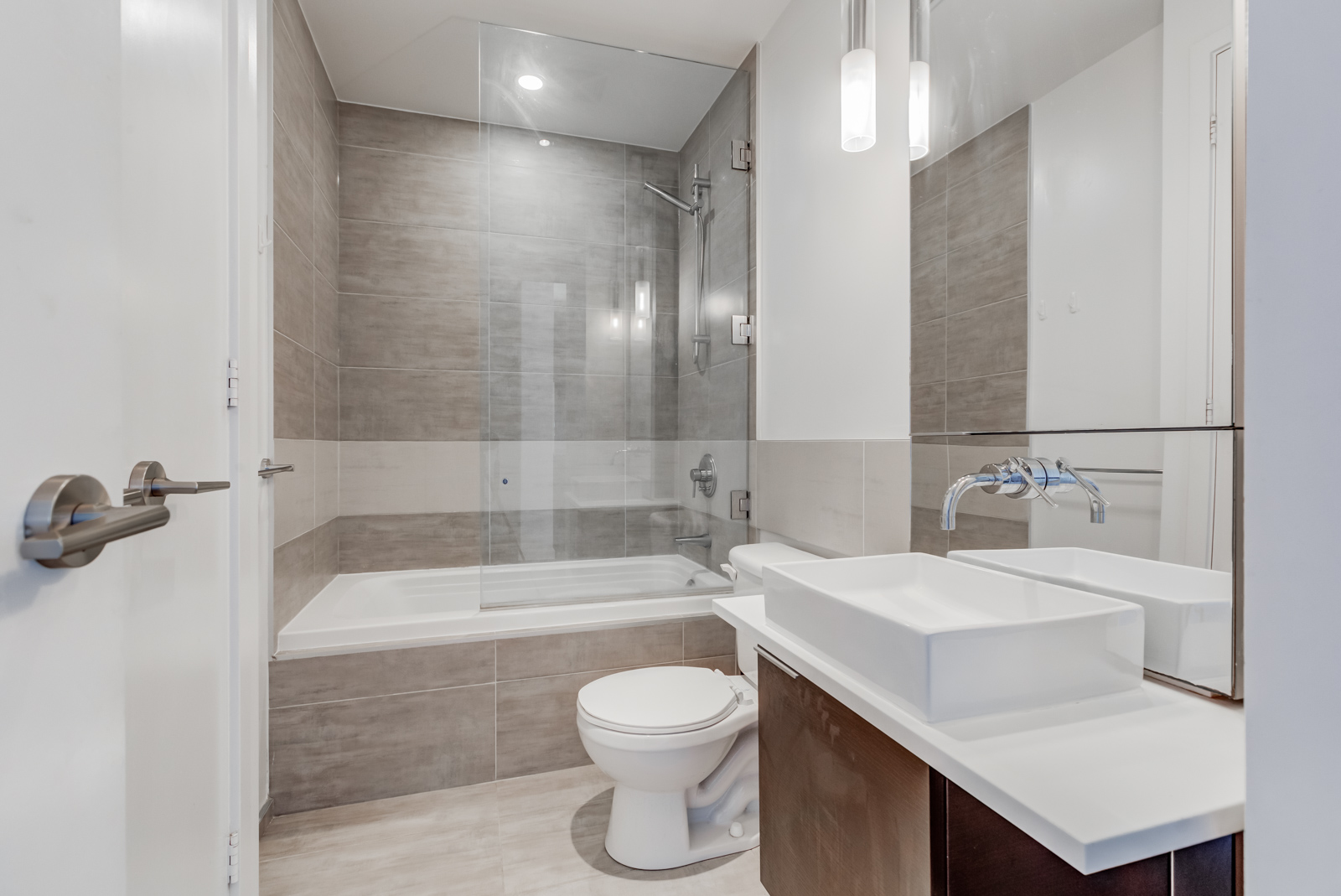 Master bathroom with modern bathtub, raised sink basin, tall mirror, detachable showerhead and brown colours.