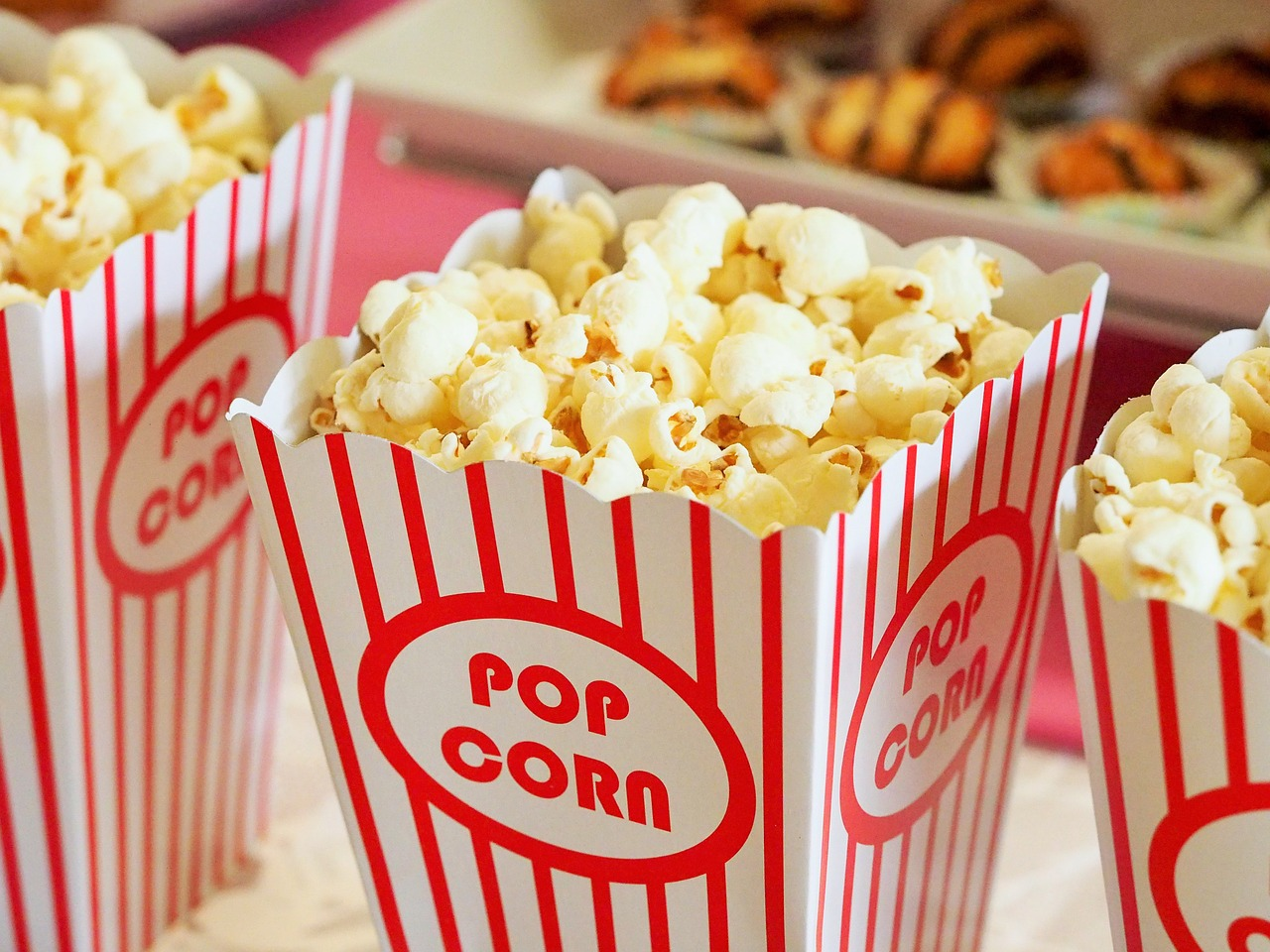 Close up of 3 striped red and white popcorn containers with popcorn.