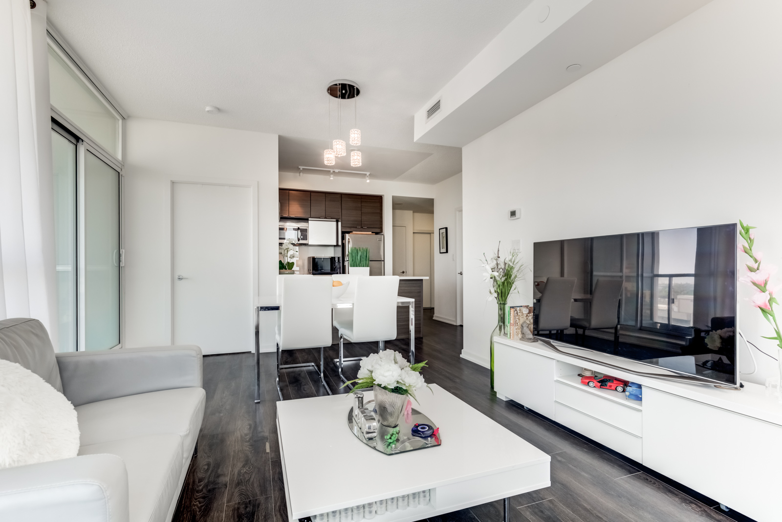 Open-concept living and dining room with dark floors and white walls at 62 Forest Manor Rd Unit 1803, Toronto.