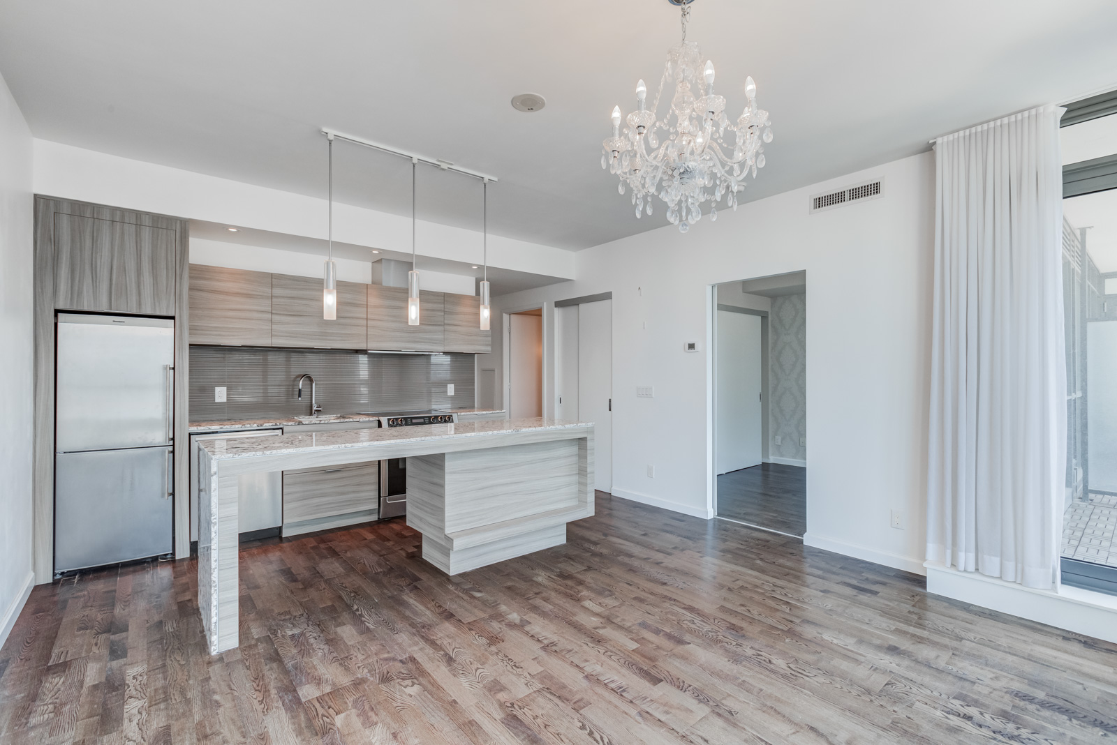 Open-concept living room, dining room and kitchen with chandelier, kitchen island, and wooden laminate floors.