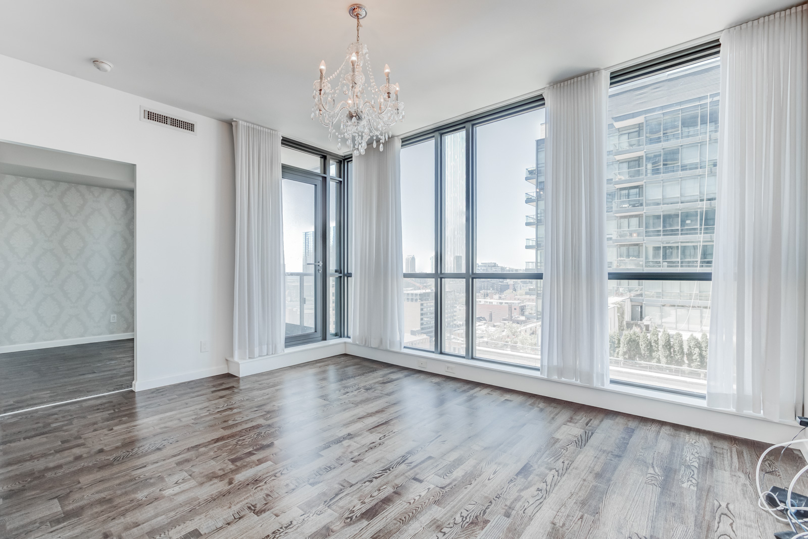 Condo interior with 9-foot ceilings, floor-to-ceiling windows, dark laminate floors, gray walls and chandelier.