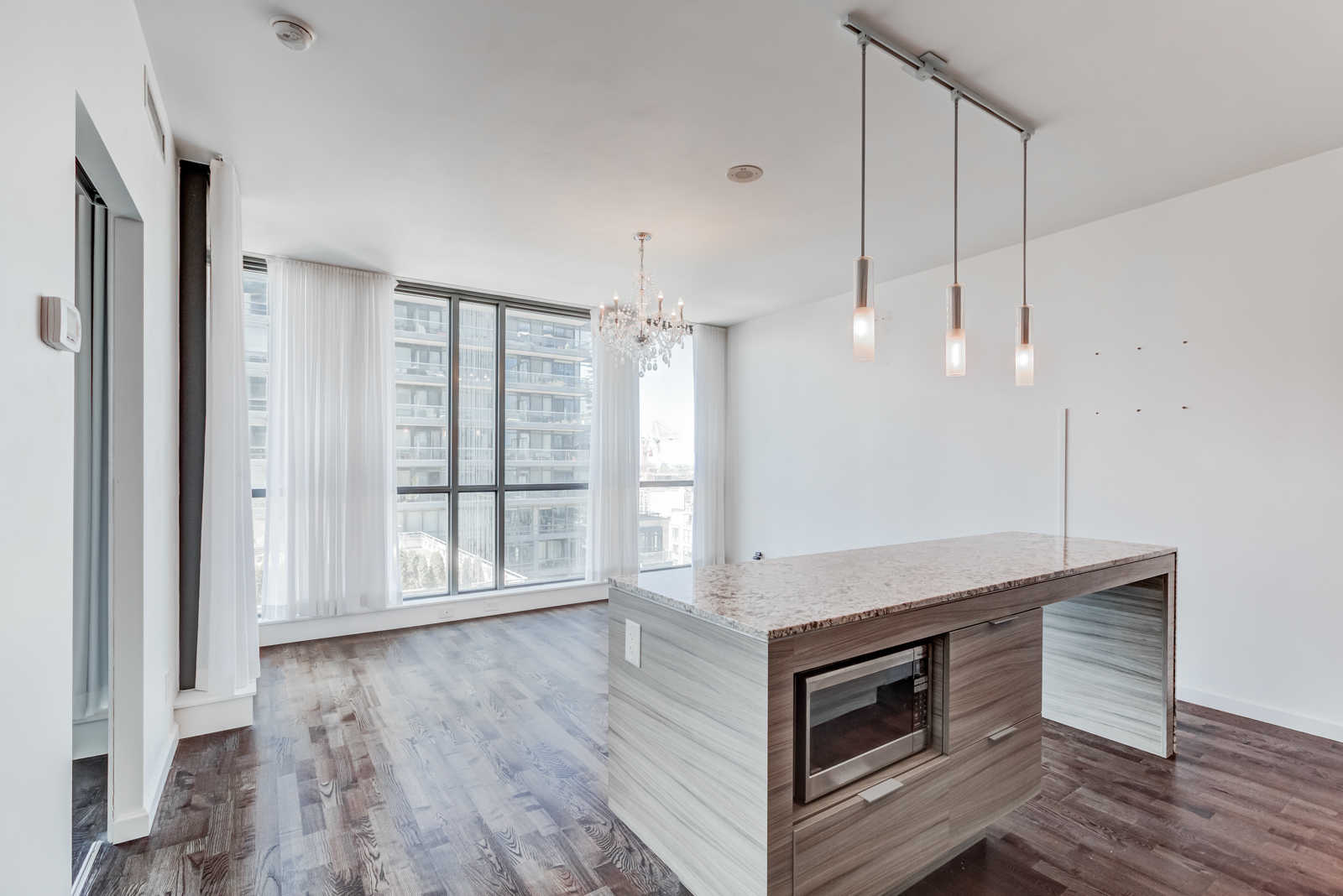 Brightly lit condo living room and kitchen island with hanging lights.