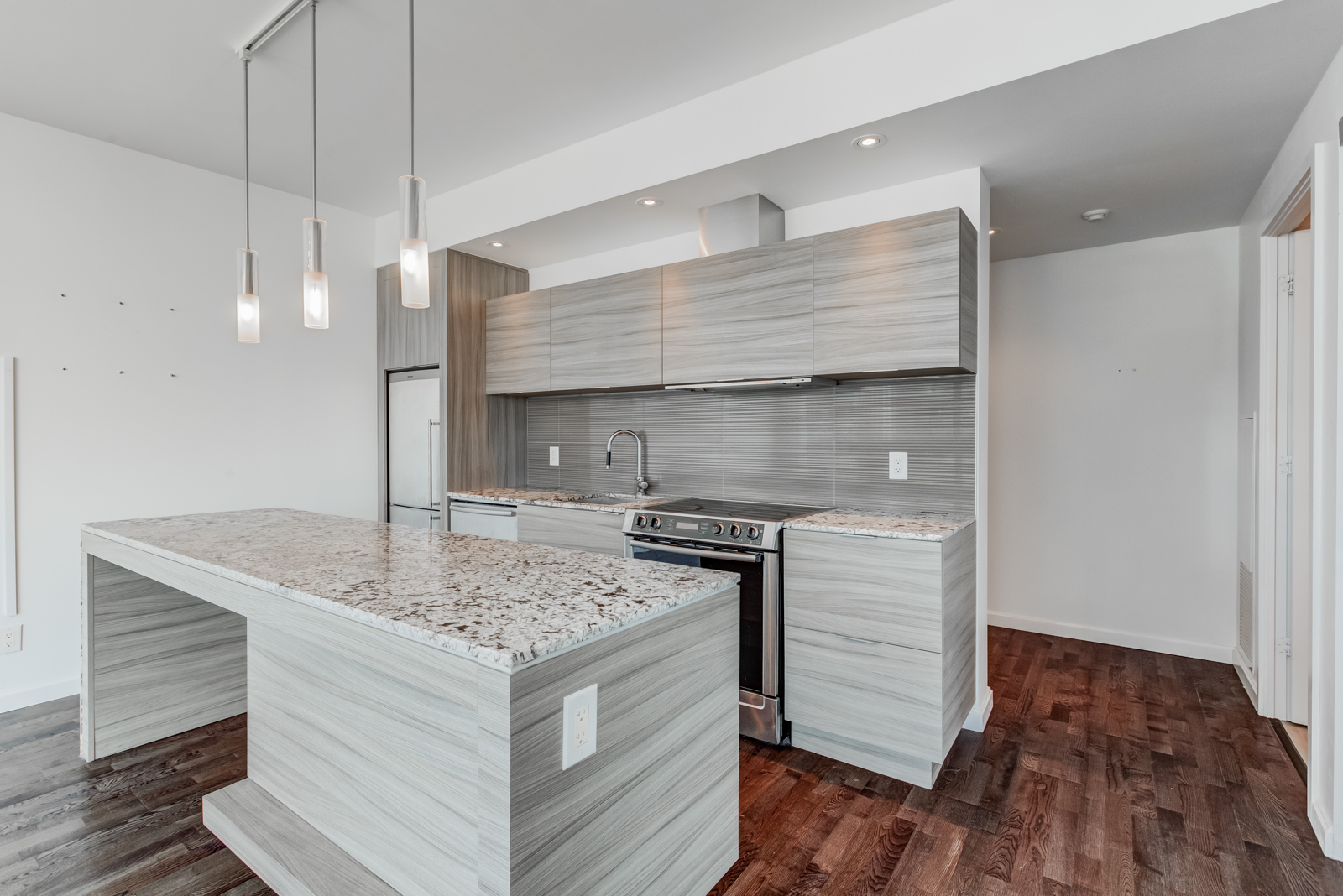 Kitchen island with speckled marble countertop and lighter base with wooden finish.