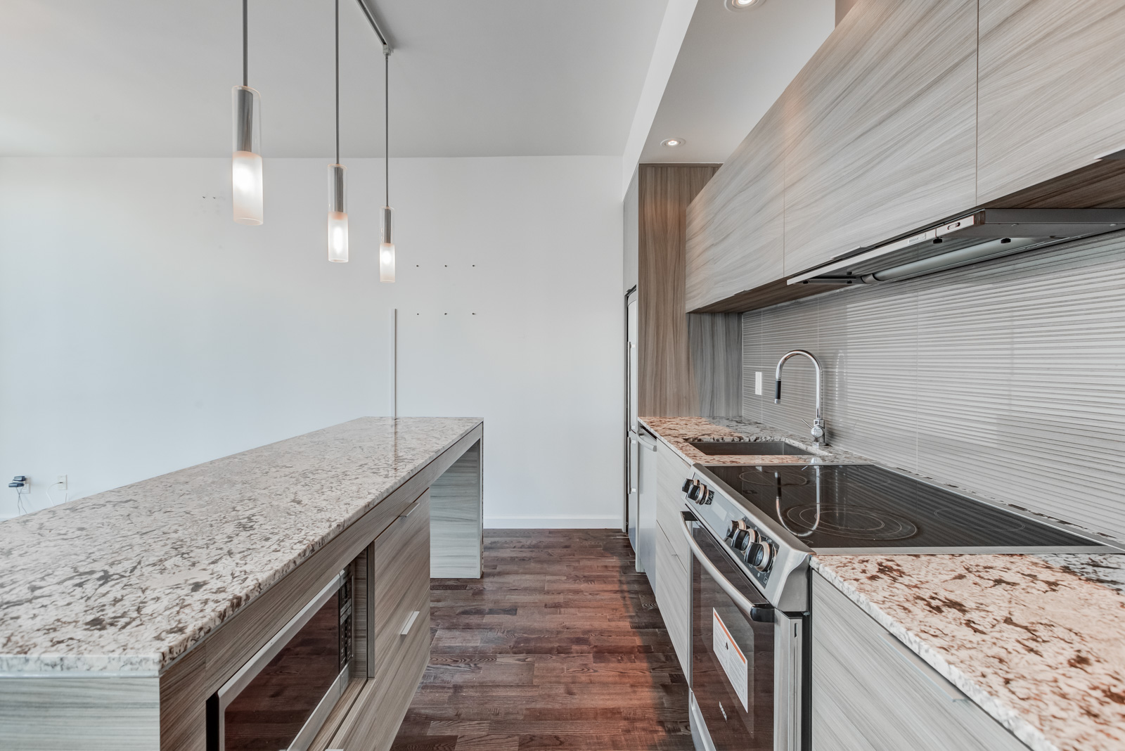 Heavily-textured kitchen with marble counters, laminate floors, stainless steel appliances, wooden cabinets and hanging lights.