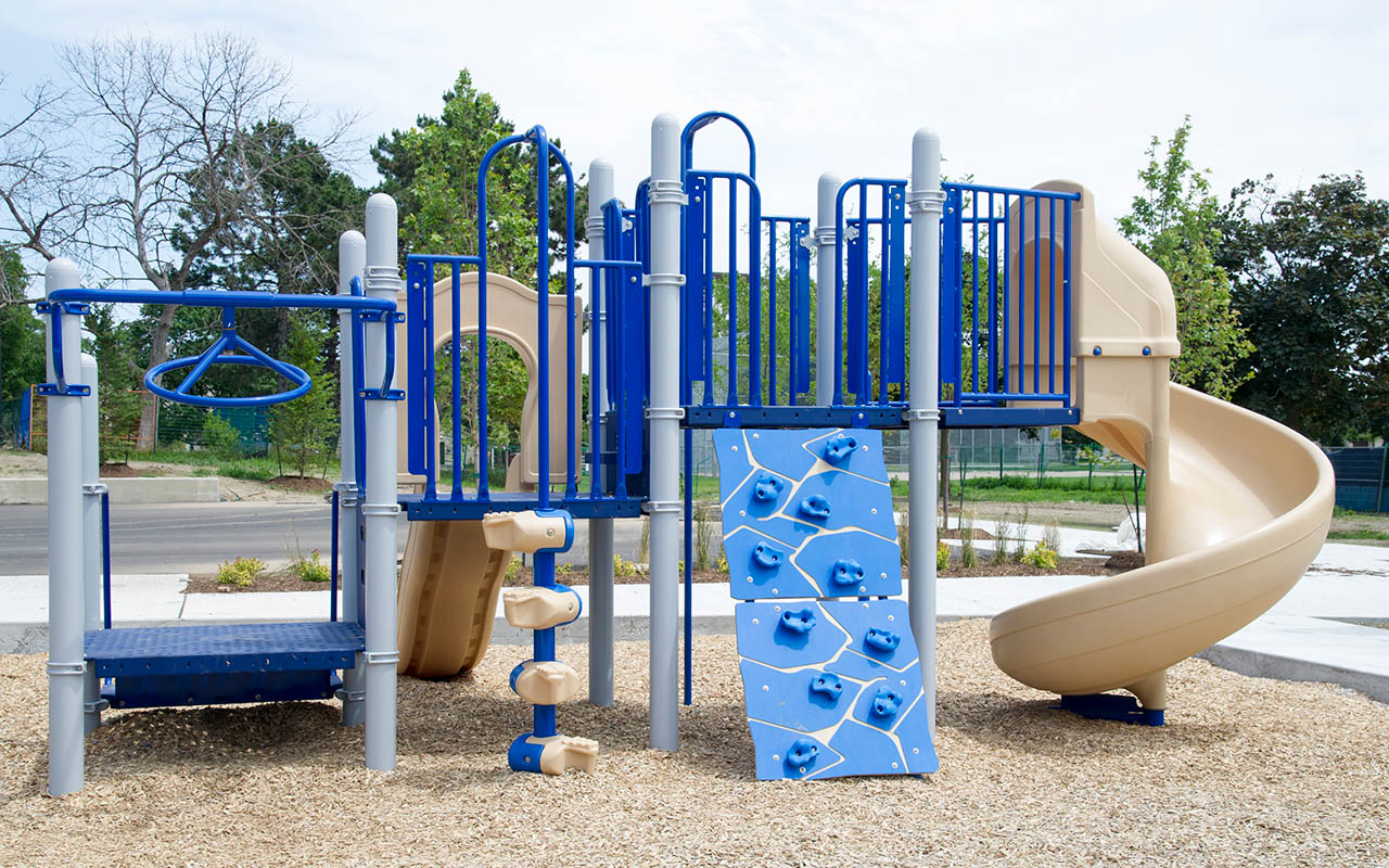 Playground with bright and dark blue slides and bars at Parkway Forest Park, North York.