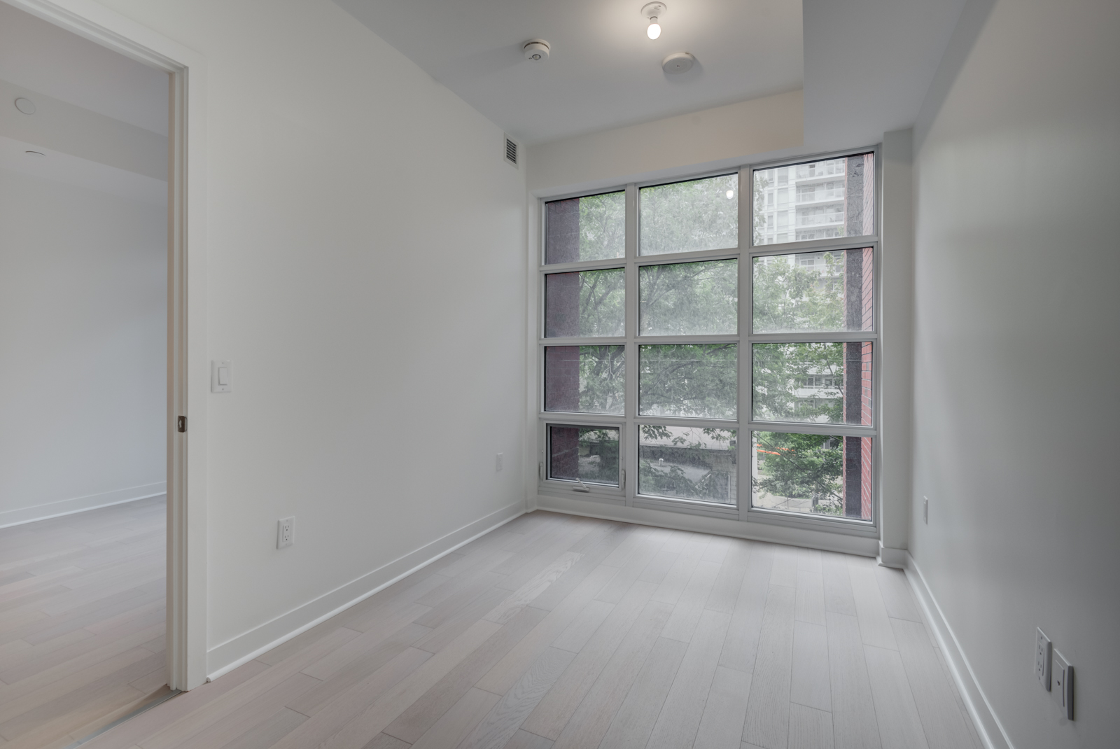Empty master bedroom with floor-to-ceiling windows.