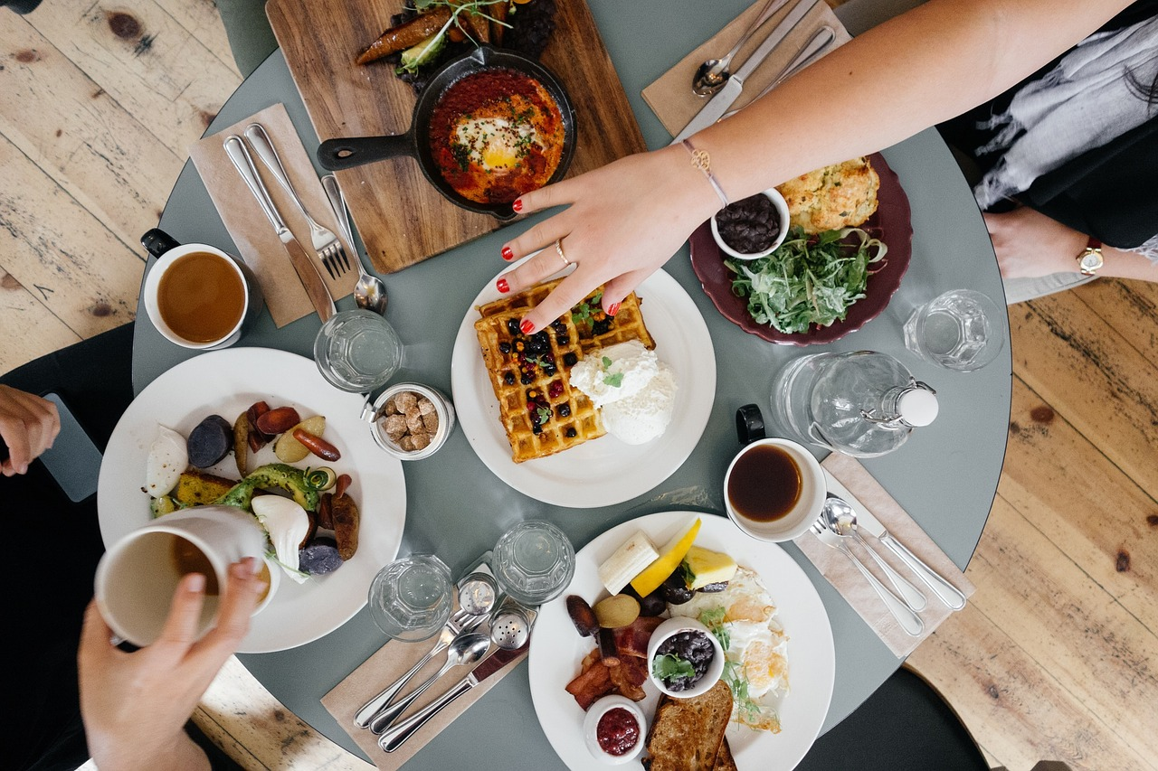 Top-down view of round breakfast table with food including fruits, vegetables and hand reaching for waffles.