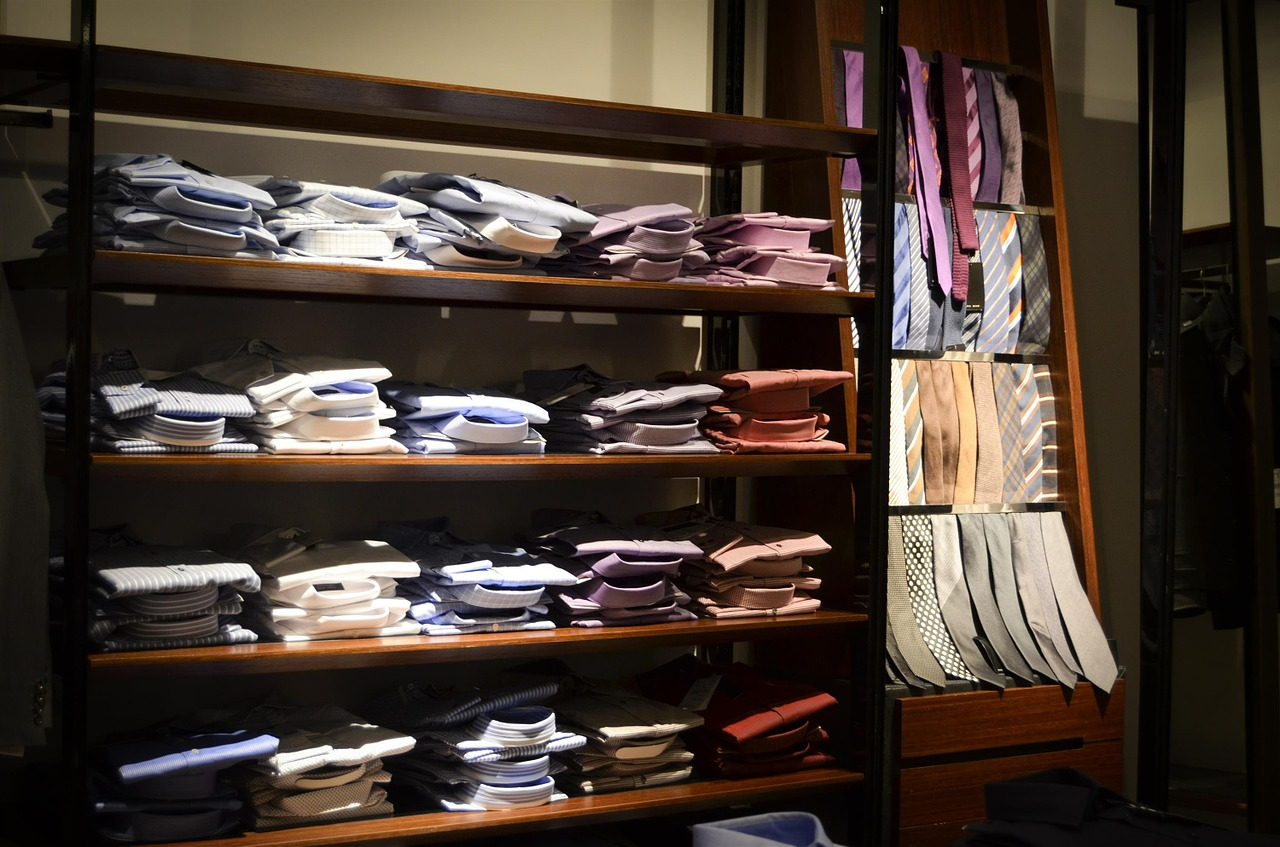 Shelves with neatly folded men's shirts and ties in many colours.