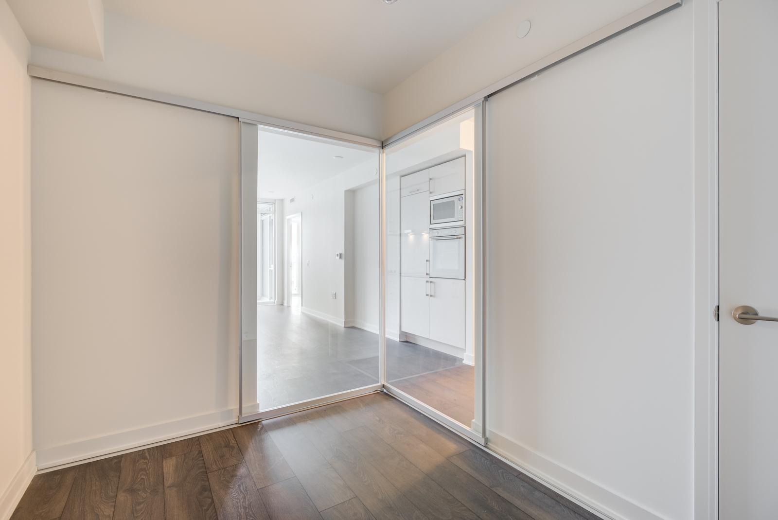 Empty second bedroom with dark laminate floors and mirror doors.