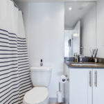 Bathroom in monochromes, striped shower curtain and sleek vanity.