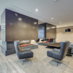 Minto Condos fireplace lounge with sleek gray walls and ceiling, furniture and art.