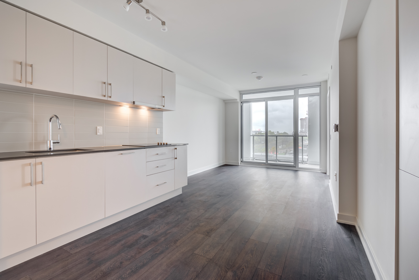 Empty living room, dining room and kitchen of 27 Bathurst Unit 308.