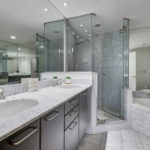 Gray and white master bath with his and her sinks, large tub and glass shower enclosure.