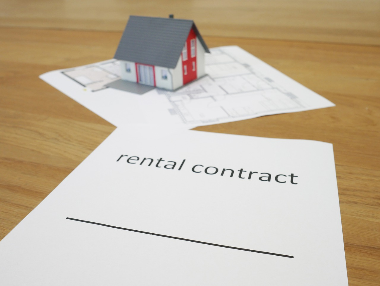 White rental contract paper with miniature house.