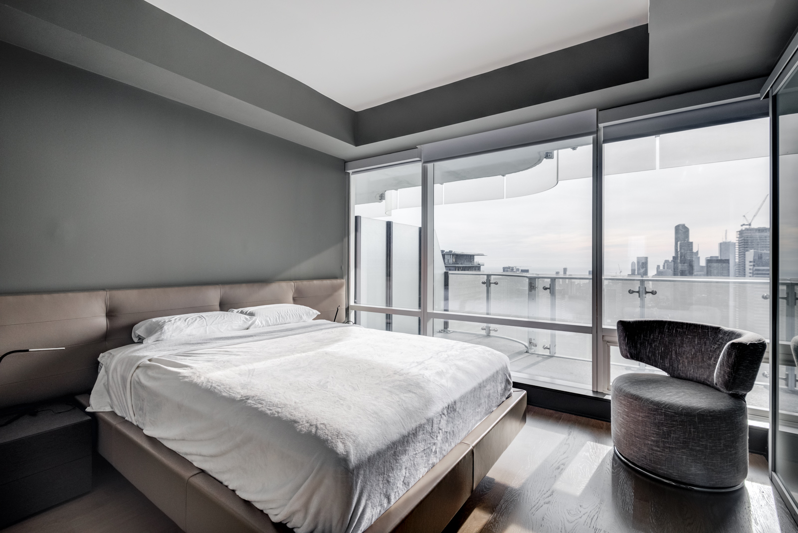 Huge master bedroom and bed with white covers; dark walls and large windows showing Toronto from One Bloor Condos.