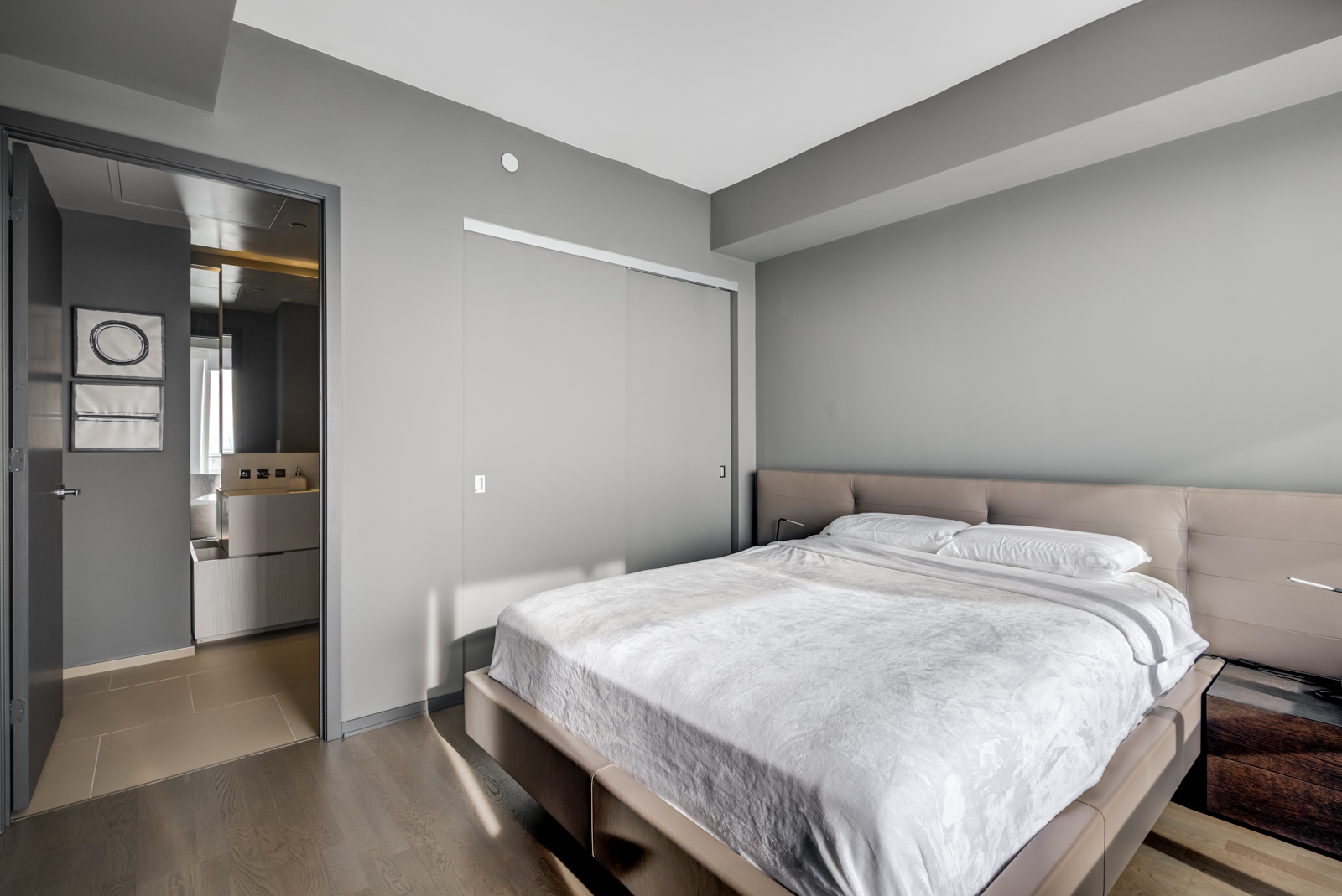 Queen-sized bed with white covers; closet with gray doors (closed).