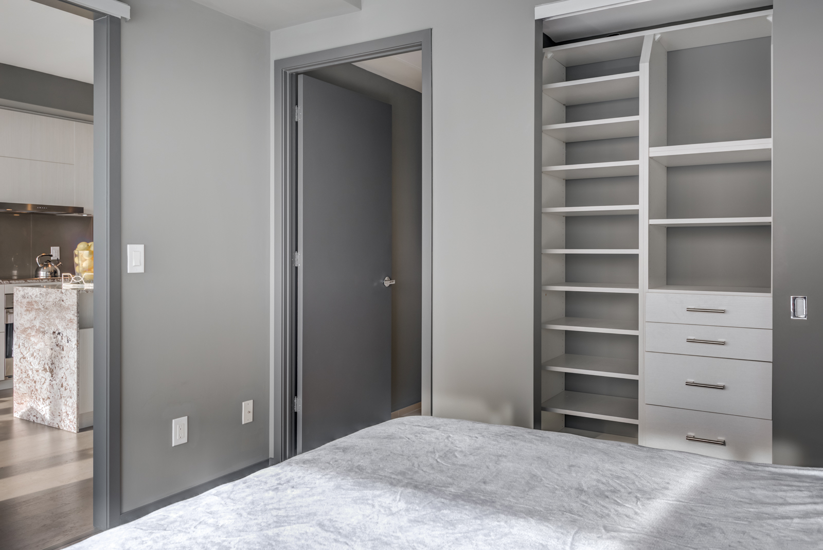 Open closet doors with empty shelves and drawers in bedroom of Unit 4305.