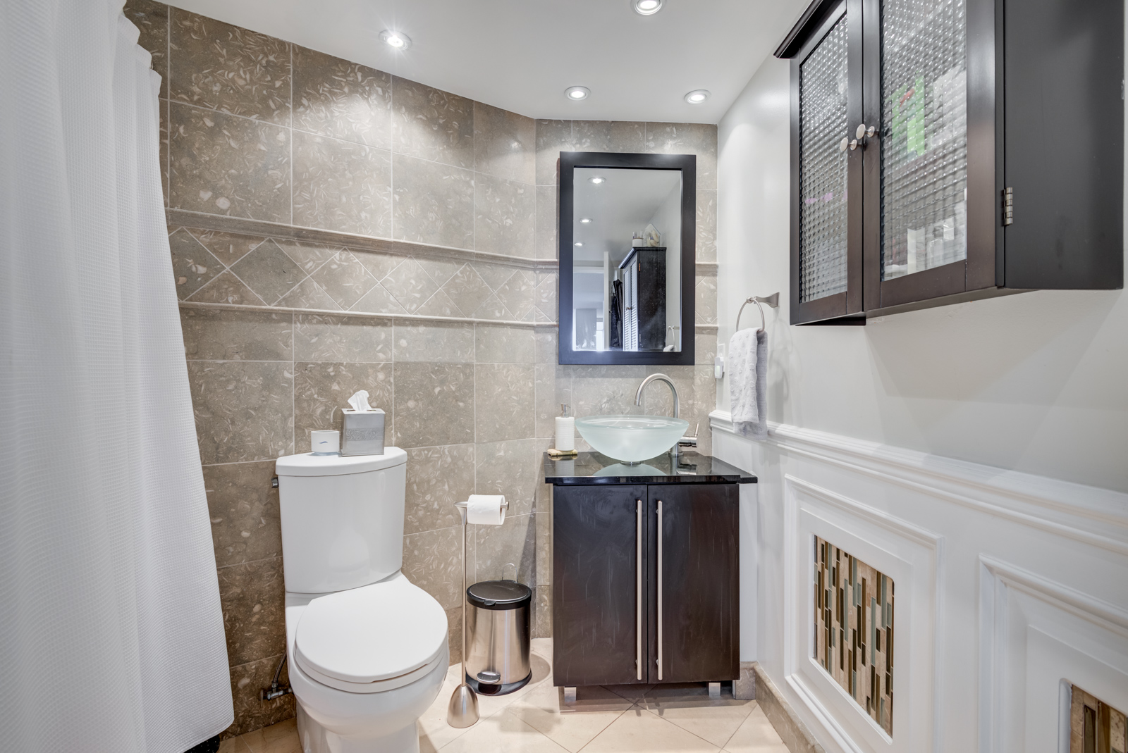 Contemporary bathroom with ceramic tiles, brown vanity, medicine cabinet, and vessel sink bowl of glass.