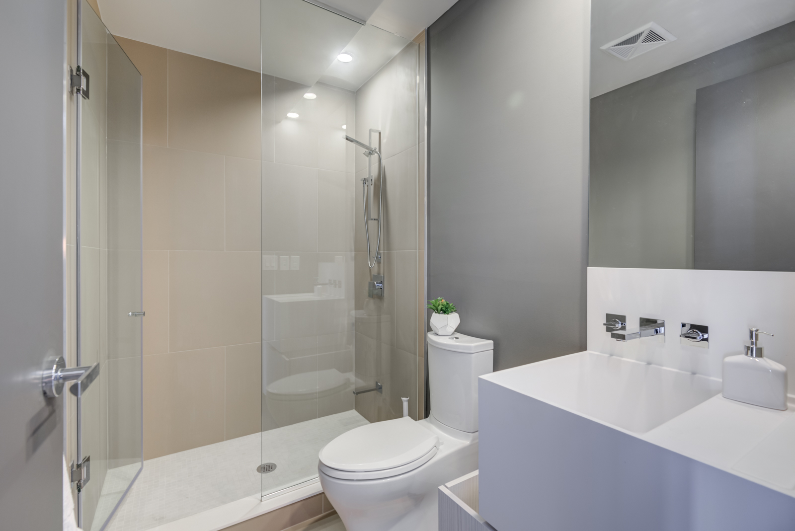1 Bloor St E Unit 4305 bathroom with walk-in shower, large white sink, cabinets and wall-mounted faucet.