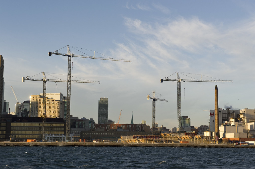 Long distance shot from Lake Ontario of 4 construction cranes on Toronto Waterfront.