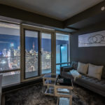 Living room at night with view of Toronto skyline through windows.