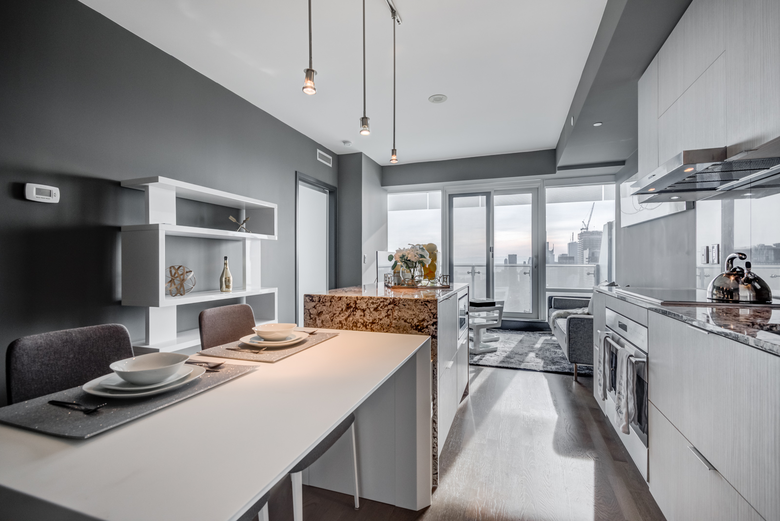 Modern kitchen with white breakfast bar, dark granite counters and stainless-steel appliances covered in sunlight.