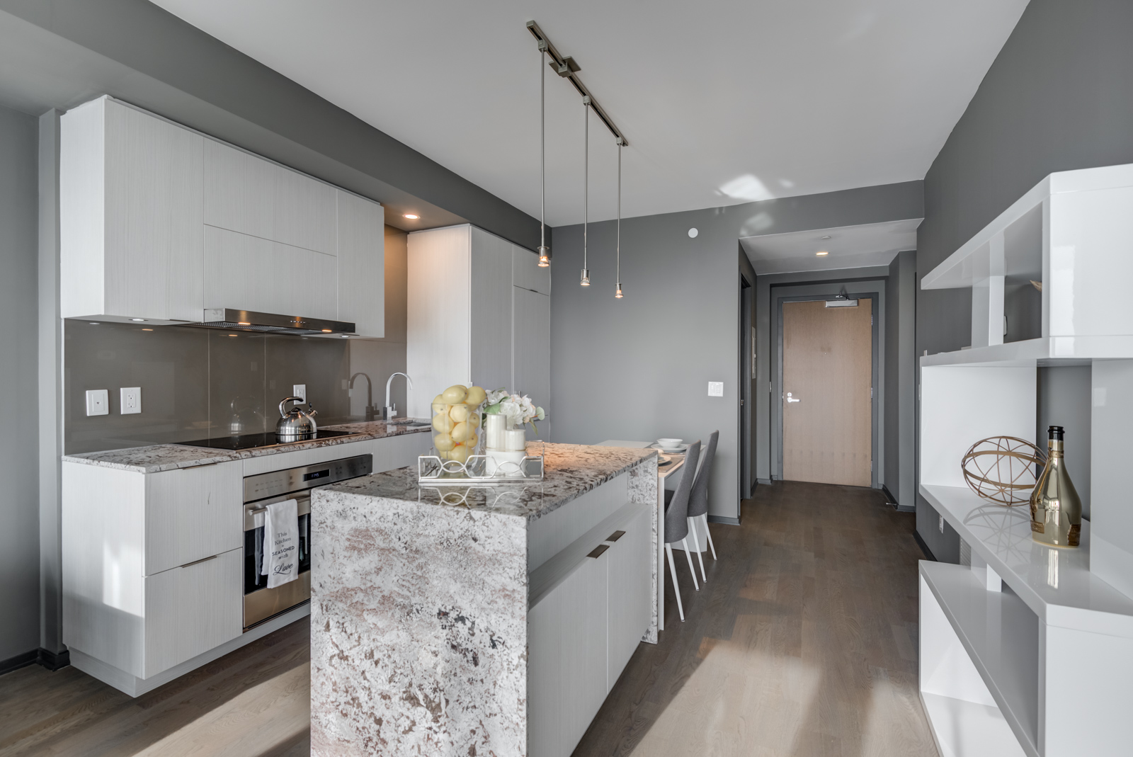 Modern kitchen of 1 Bloor St E Unit 4305 with granite counters, island, pendant lights and wooden cabinets.