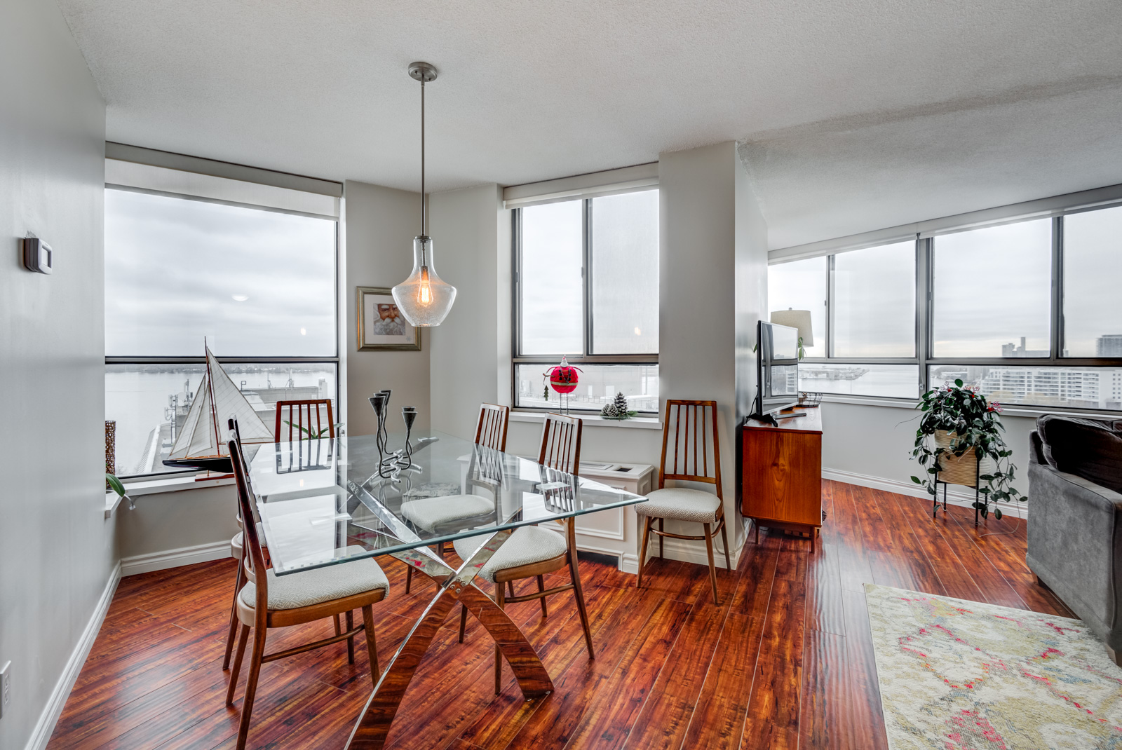 Dining room with clear glass table, red floors and window with view of Toronto Waterfront.