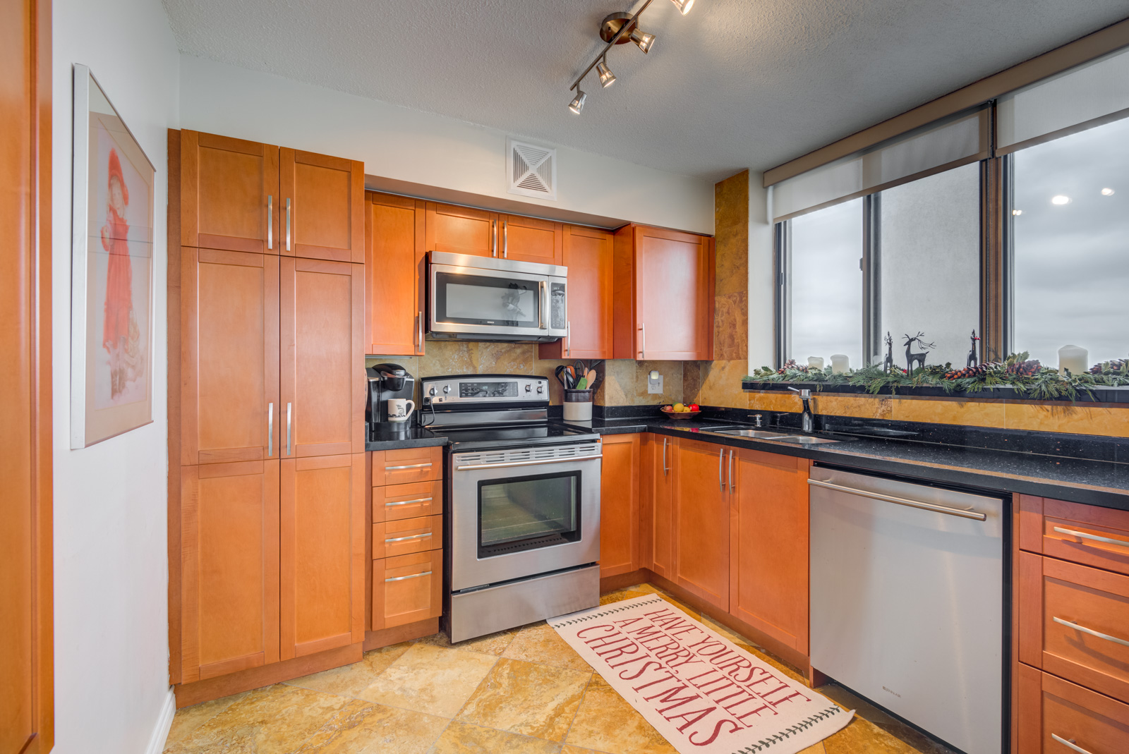 Large kitchen with orange oak cabinets, drawers, silver appliances, slate floors and track-lights.