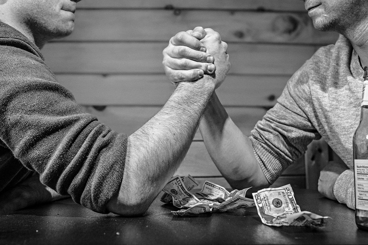 Two men arm wrestling; shows competition for homes in November 2019 GTA real estate market and sellers' market.