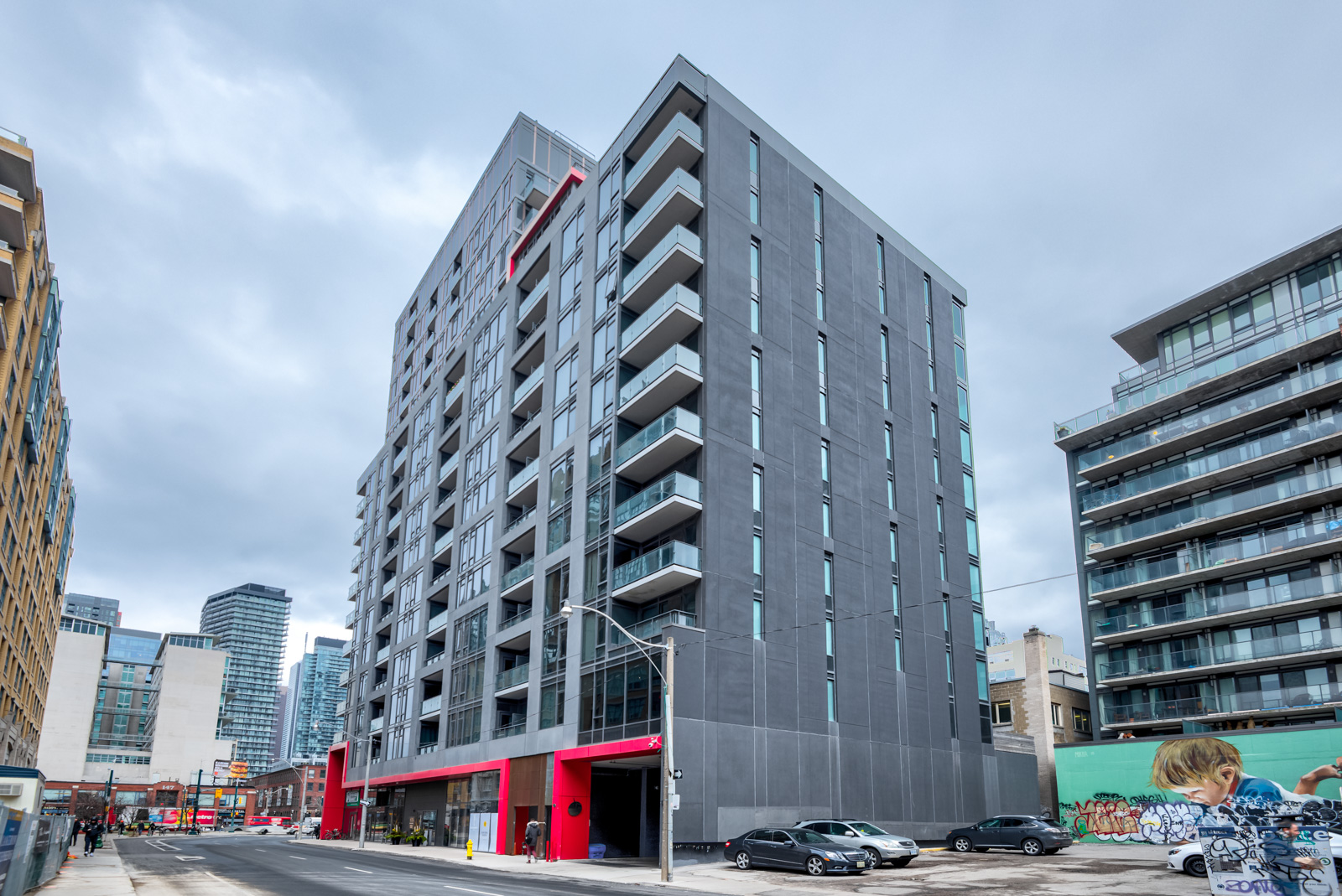 Street view of Fabrik Condos, a dark gray building with bright red accents on 435 Richmond St W PH 101.
