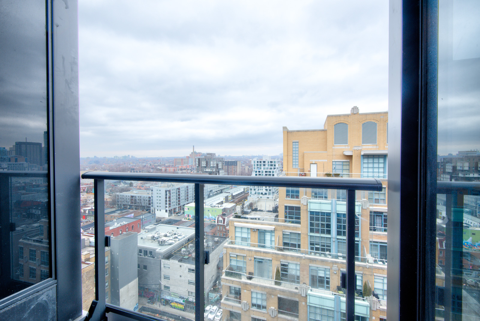 PH 101 balcony with glass panels overlooking buildings of the Fashion District.