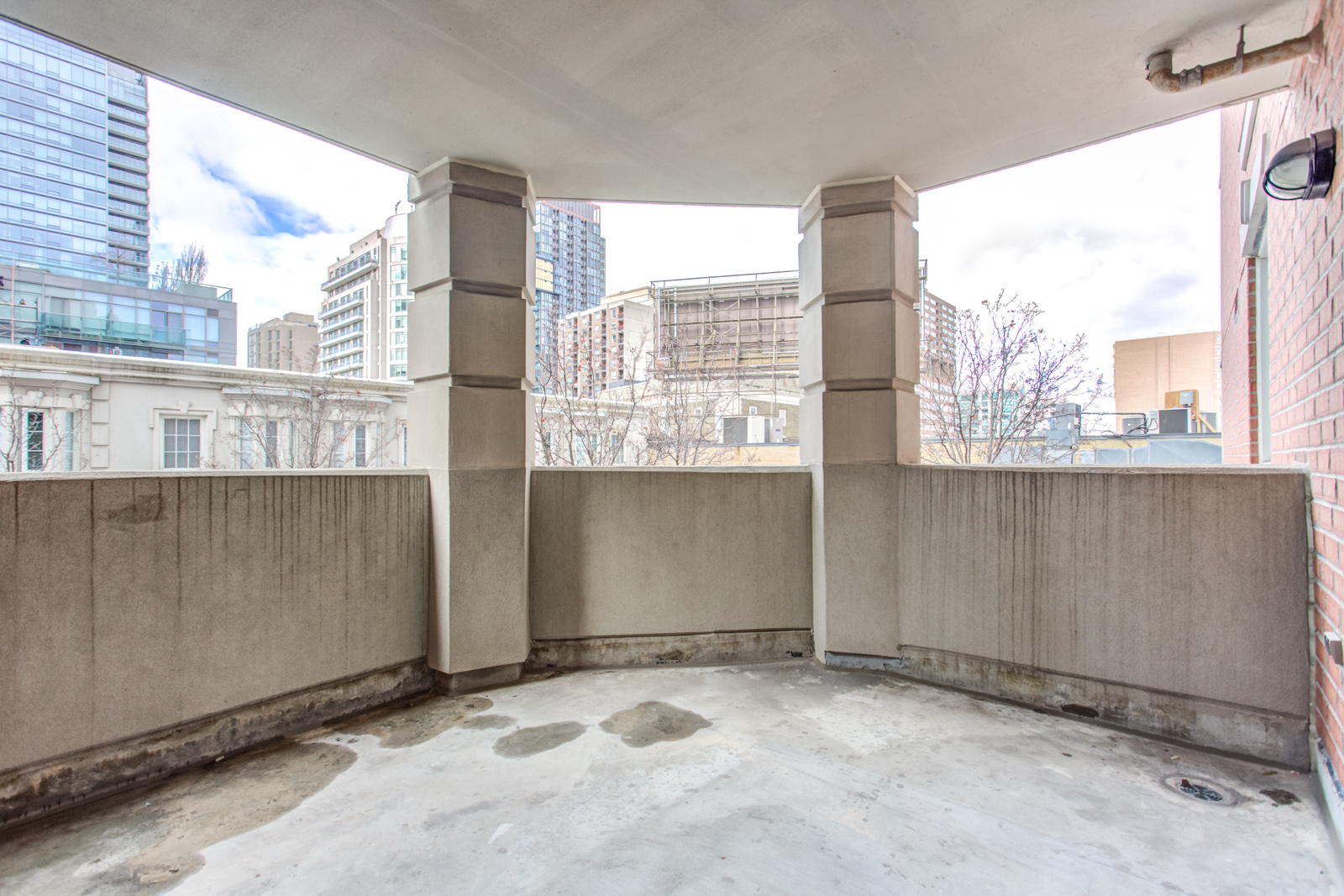 Concrete balcony of 20 Collier St Unit 408 with columns and view of Yorkville beyond.