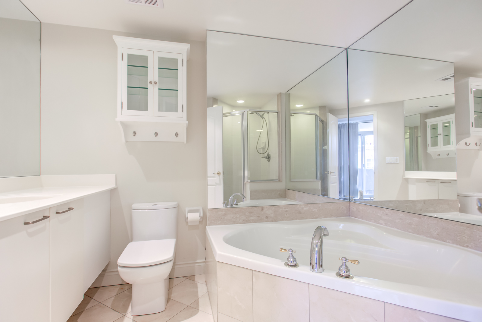 Ensuite bath with Jacuzzi, white sink and cabinet, and wall-to-wall mirrors.