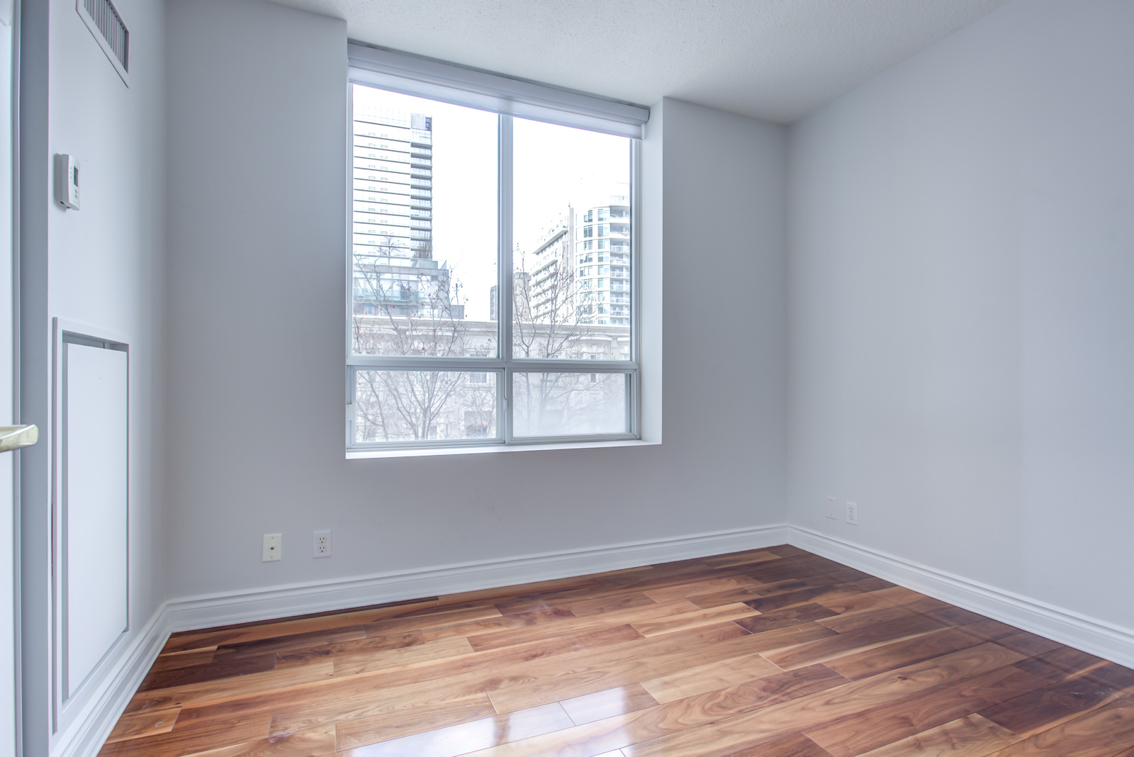 Bedroom with newly-painted gray walls and shiny dark brown hardwood floor at 20 Collier St Unit 408.