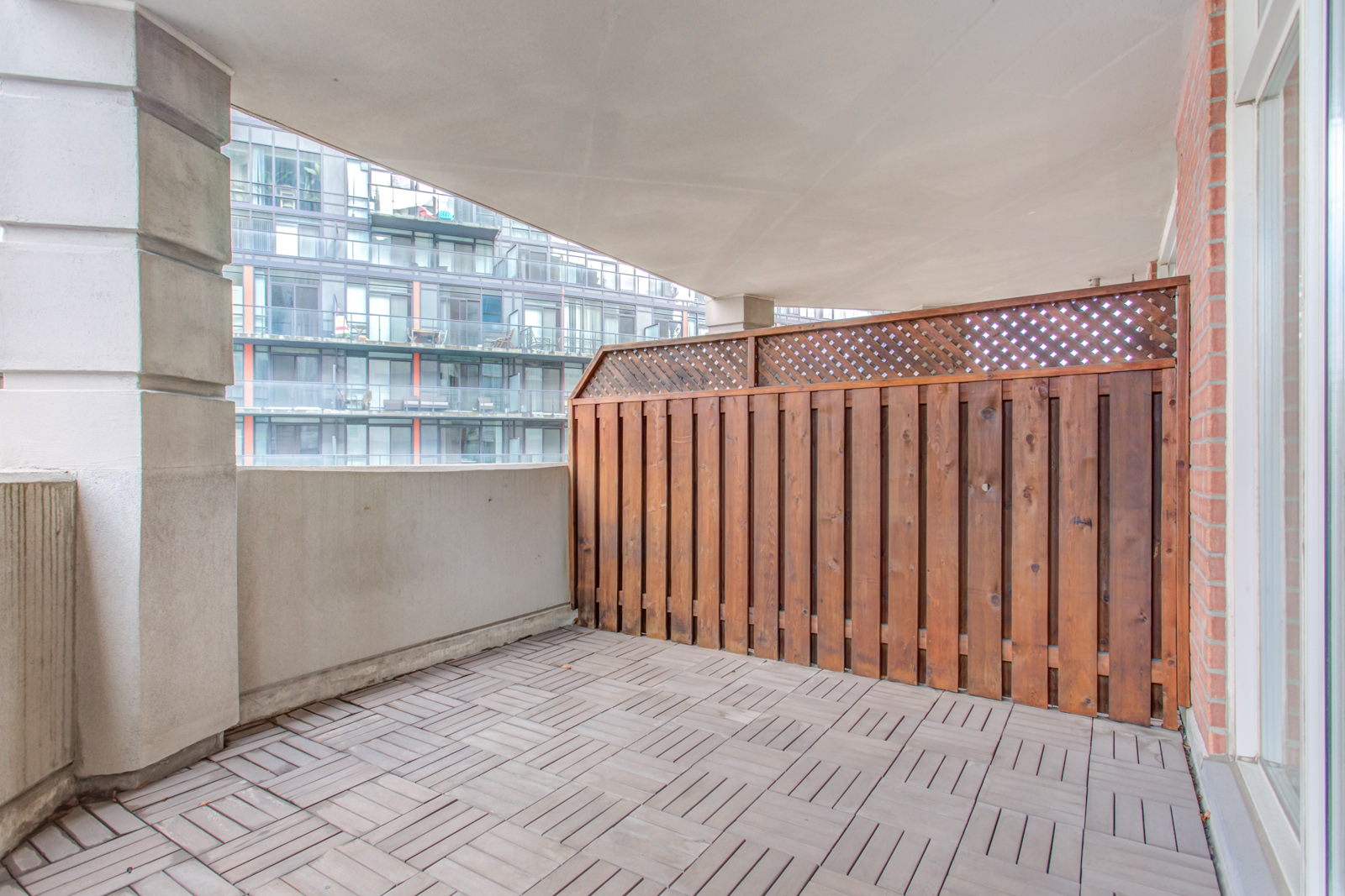 Balcony and deck of 20 Collier St Unit 408 with tiled floors and red wood fence.