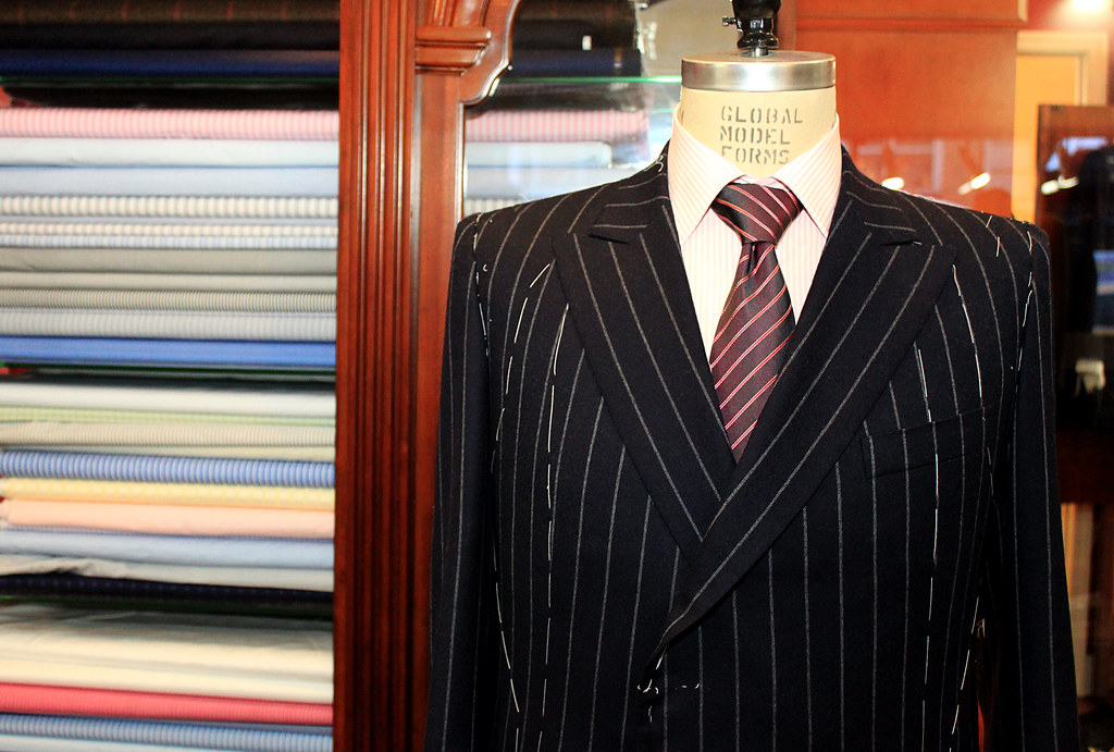 Headless mannequin wearing custom-tailored pin-stripe suit in shop of the Fashion District.