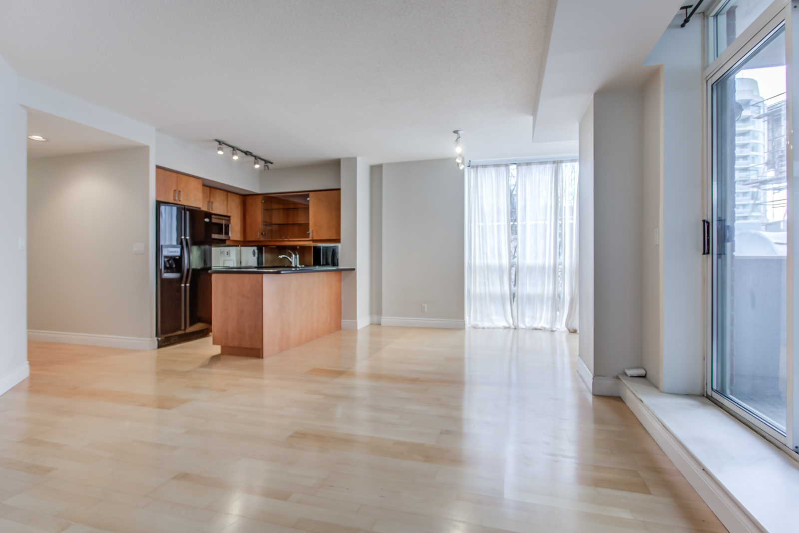 Empty living, dining & kitchen area of 20 Collier St Unit 408 with shiny hardwood floors.