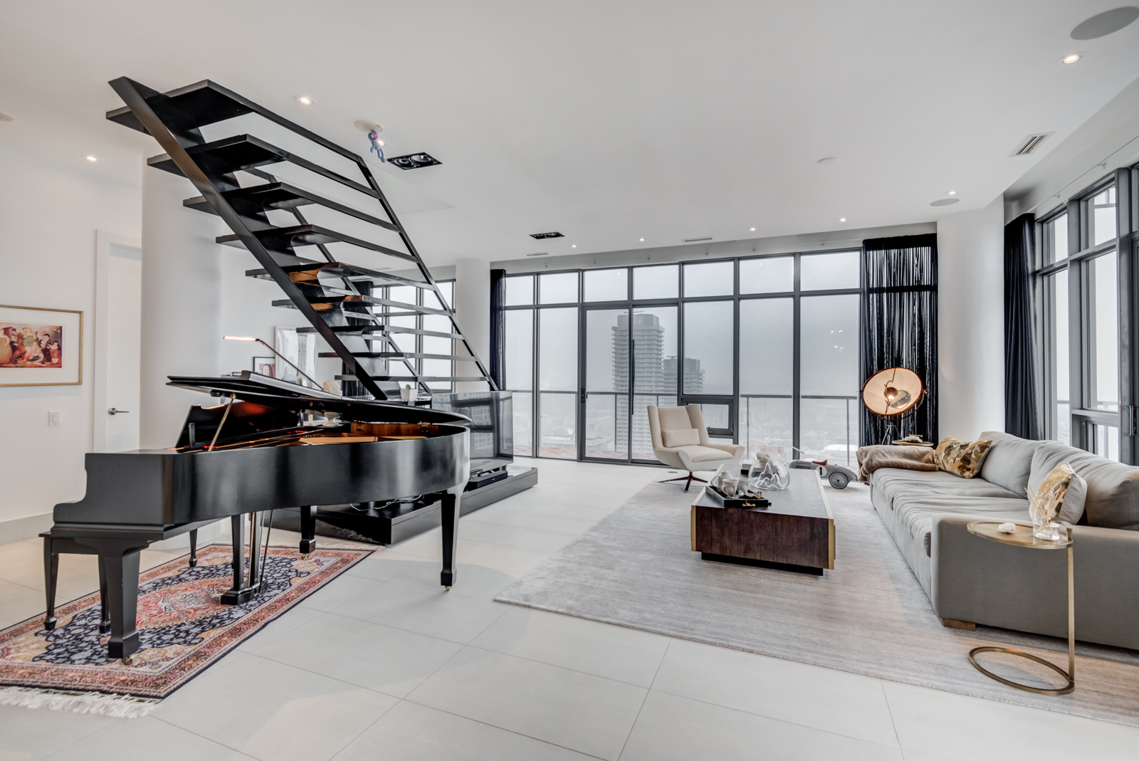 Second most expensive property with black piano, staircase, furniture in penthouse of 33 Charles St E penthouse unit.