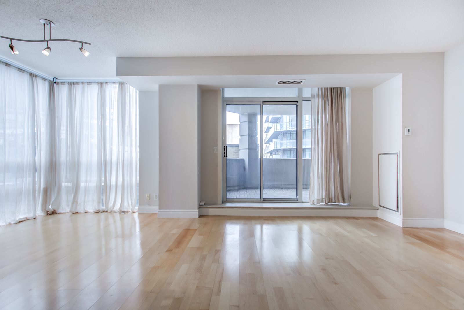 Spacious and empty living room of 20 Collier St Unit 408 showing balcony and white curtains.