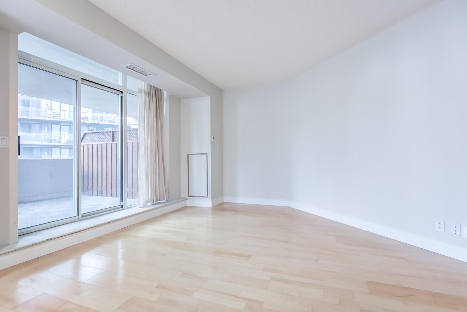 Empty living room with view of balcony through screen doors.