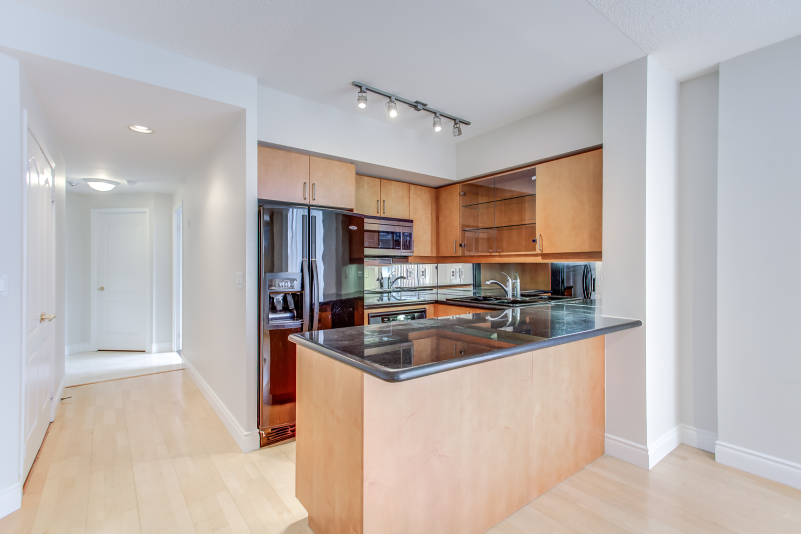 Kitchen with black counters, black fridge, wooden cabinets and track-lights.