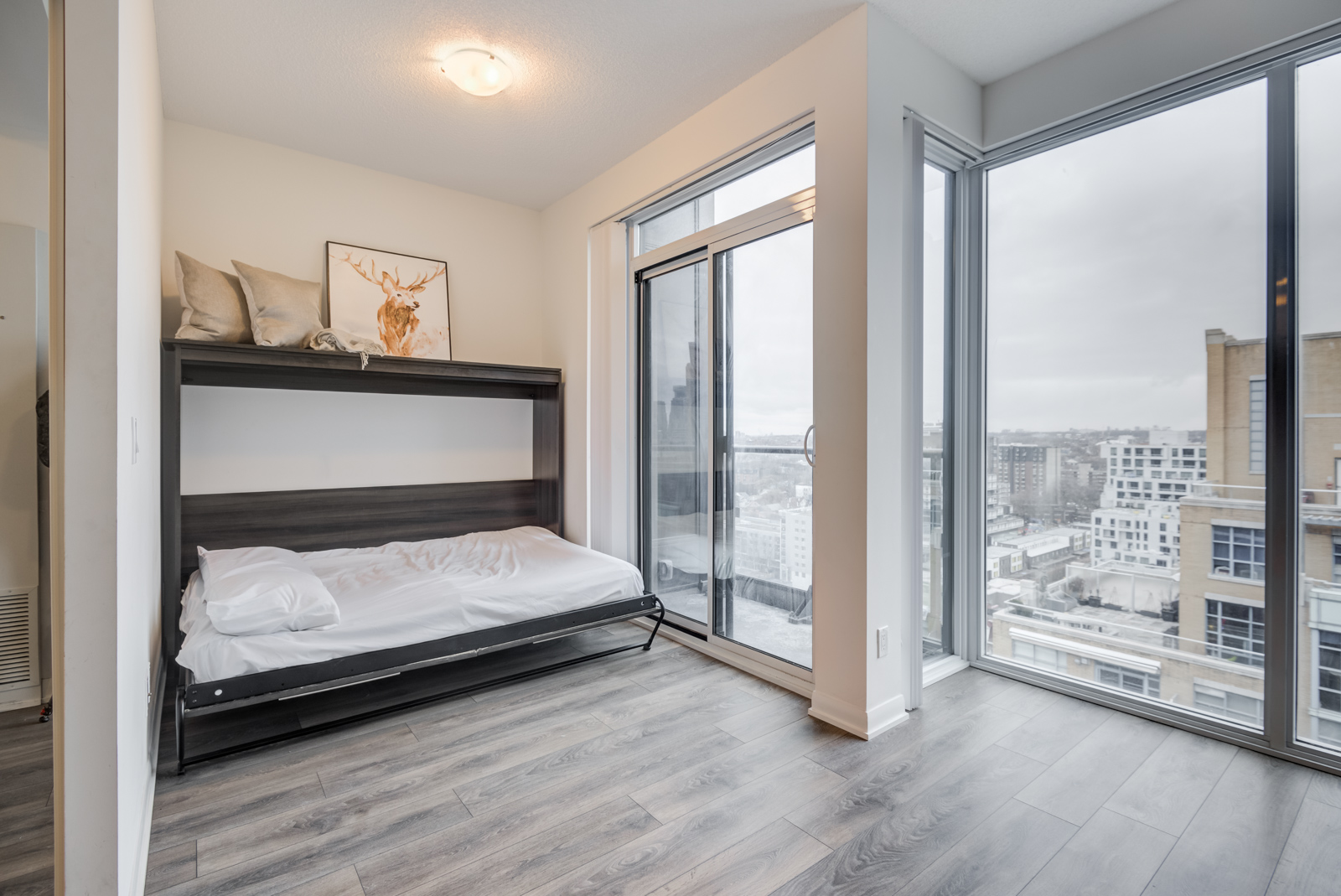 The penthouse suite with an open Murphy bed with white covers and pillow.