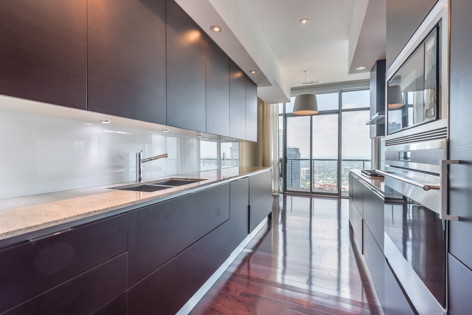 Galley kitchen with dark cabinets on either side of penthouse suite at 33 Charles St E Casa Condos.