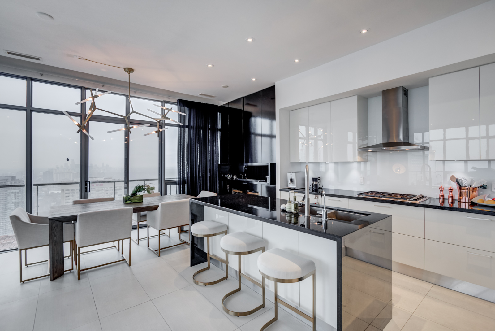Penthouse kitchen of 33 Charles St E Casa Condos with black counters, breakfast bar and appliances.