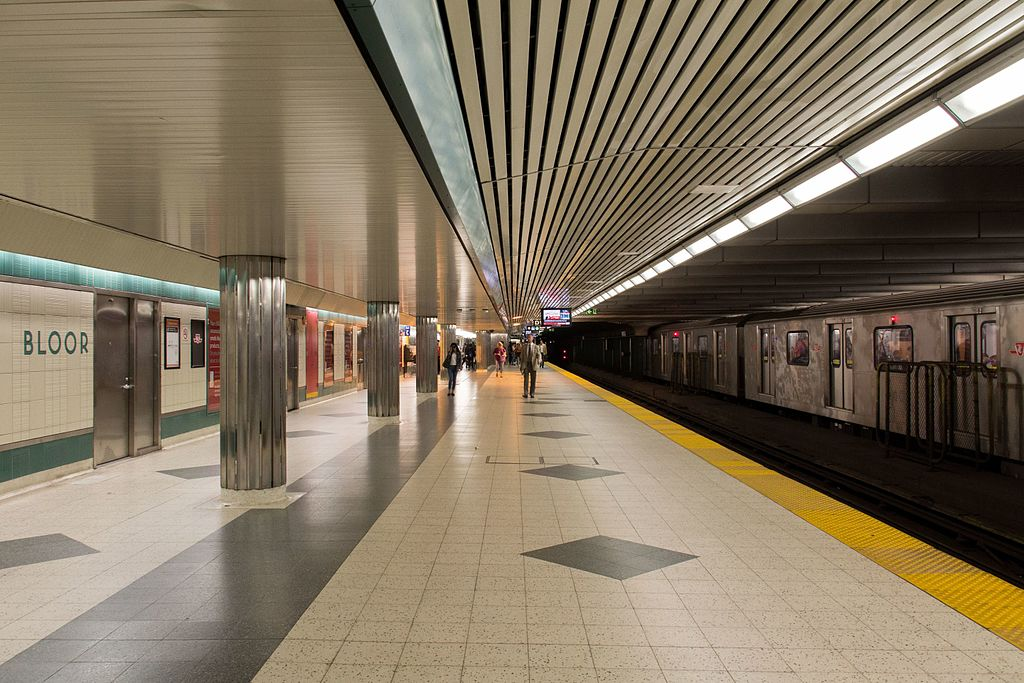 Brightly subway platform with people and train old TTC train to right in Toronto.