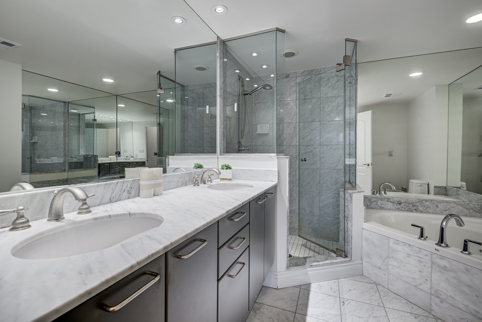 Gorgeous master bath with marble tiles, tub, 2 sinks, walk-in shower of 77 Mcmurrich St Unit 308.