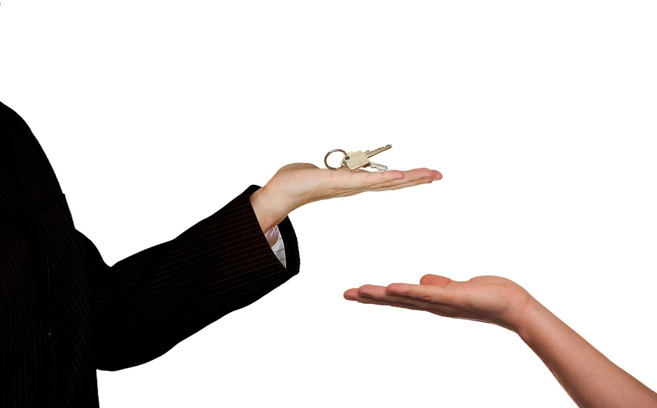 Close up of male hand holding house keys and female hand with palm facing upwards