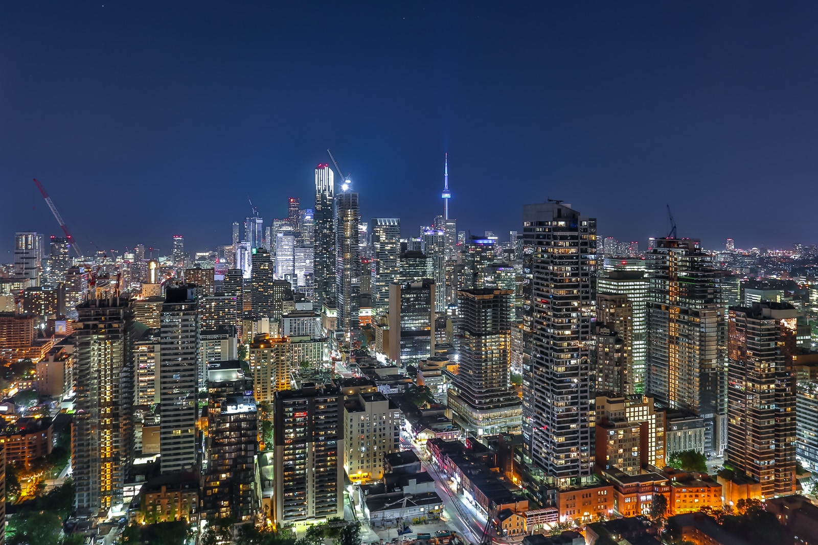 Toronto skyline at night from 33 Charles St E penthouse of Casa Condos with CN Tower in distance.